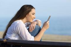 Contenu de observation de téléphone de fille décontractée sur la plage images libres de droits