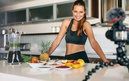 Contenu femelle d'enregistrement de blogger pour son blog dans la cuisine photos libres de droits