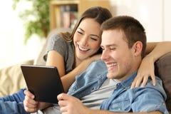 Contenuto di sorveglianza di risata delle coppie in una compressa fotografie stock
