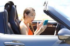 Contenuto di sorveglianza stupito di media del driver in uno Smart Phone fotografia stock libera da diritti