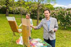 Conteplative male and female artists painting in the open air. Conteplative male and female artists painting on their easels pictures  in the open air with Royalty Free Stock Image