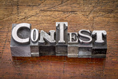 Contest in metal type. Contest word in mixed vintage metal type printing blocks over grunge wood stock images
