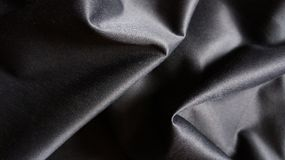 Contesto serico nero del tessuto del panno del primo piano con le curve Fotografia Stock Libera da Diritti
