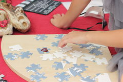 Contests and entertainment festival. folding puzzles. The child puts puzzles. soft focus royalty free stock photography