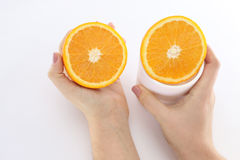 In the context of orange. Good juicy orange cut in half midway white one piece  in a girl`s hands another in a white cup Stock Photos