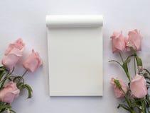 Contexte de mariage avec les roses et le bloc-notes vide de page blanc Photo stock