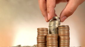 Conti e metta le monete dei soldi alla pila di monete video d archivio