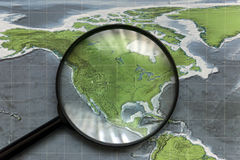 Continent of North America on the map under a magnifying glass. Continent of North America on a paper map under a magnifying glass Royalty Free Stock Photo