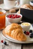 Continentaal ontbijt met croissant, jam en vruchten stock afbeeldingen