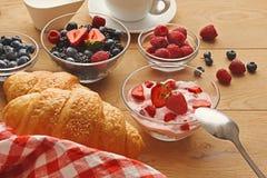 Continentaal ontbijt met croissants en bessen op natuurlijk hout royalty-vrije stock afbeelding