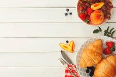 Continentaal ontbijt met croissants en bessen op wit hout stock afbeelding