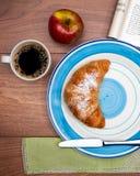 Continentaal ontbijt met koffie, verse croissants, fruit en goed tijdschrift stock foto's