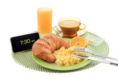 Continental Breakfast. Continental hotel breakfast with scrambled eggs, croissant, coffe, orange juice and alarm clock showing early morning Stock Photography