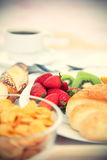 Continental breakfast. Breakfast tray. Continental breakfast tray with coffee, cornflakes, croissant, strawberries, kiwi and bread. Shallow depth of field Royalty Free Stock Image