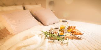 Continental breakfast on bed in elegant bedroom interior Stock Photos