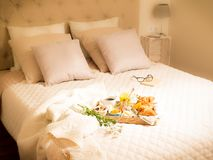 Continental breakfast on bed in elegant bedroom interior Royalty Free Stock Photography
