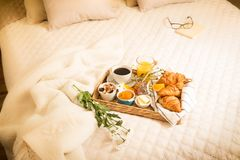 Continental breakfast on bed in elegant bedroom interior Royalty Free Stock Image