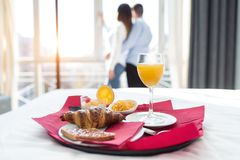 Continental breakfast in bedroom at hotel room. In the background, young couple looking cityscape through the window stock photography