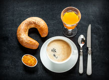 Continental breakfast on black chalkboard. Background - bar menu. Coffee, orange juice, crescent roll and jam from above Stock Image
