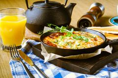 Continental breakfast in a cafe, omelet with ham in pan stock photos