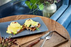 Continental breakfast. Close up view on traditional belgian breakfast served on grey plate on wooden table in cafe. Eggs Benedict stock photos