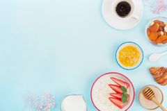 Continental breakfast with coffee, croissant, oatmeal, jam, honey and fruit on blue table top view. Empty space for text. Flat lay royalty free stock photos