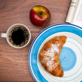 Continental breakfast with coffee, fresh croissants, fruit and good magazine Royalty Free Stock Image