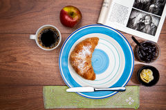 Continental breakfast with coffee, fresh croissants, fruit and good magazine. Close up Royalty Free Stock Images