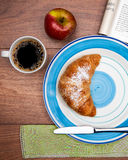 Continental breakfast with coffee, fresh croissants, fruit and good magazine Stock Photos
