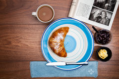 Continental breakfast with coffee, fresh croissants, fruit and good magazine. Close up Stock Images
