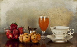 Continental breakfast,coffee,juice,muffins,fruits. A delicious morning meal: a cup of strong coffee, milk, an orange juice glass, little chocolate chip muffins stock image