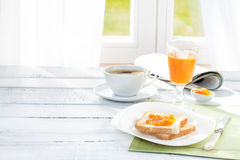 Continental breakfast - coffee, orange juice, toast. Continental breakfast - coffee, orange juice and toast on white wood table. Window as background Royalty Free Stock Photo