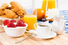 Continental breakfast. Coffee, strawberry with cream, croissant Royalty Free Stock Image
