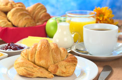 Continental Breakfast with Croissant. Coffee, orange juice, milk, jam, butter and green apple (Selective Focus, Focus on the front of the croissant Royalty Free Stock Image