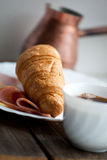 Continental breakfast with croissant and coffee, soft focus Royalty Free Stock Image