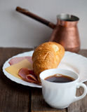 Continental breakfast with croissant and coffee, soft focus Royalty Free Stock Photo