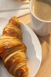 Continental Breakfast Croissant and Cup Of Coffee. A breakfast croissant and cup of hot coffee illuminated by golden early morning sunshine Royalty Free Stock Photos