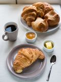 Continental breakfast with French croissants, butter, jam, black. Above view of a Continental breakfast with French croissants, butter, jam, black coffee and a Stock Images