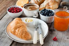 Croissants with coffee, butter, jam and fresh fruits. Continental breakfast fresh croissants with butter, cup of coffee, jam and fruits on wooden table. Closeup Stock Images