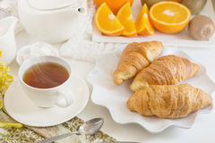 Continental breakfast with gold french croissants fruits and cup Royalty Free Stock Photo