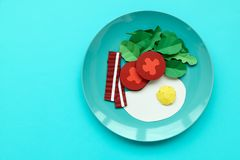 Continental breakfast made from paper: fried egg, tomato, bacon, spinach and arugula on blue background. Minimal, creative,. Healthy or food art concept. Copy stock photos