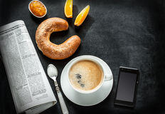 Continental breakfast and mobile phone on black chalkboard. Continental breakfast on black chalkboard - bar menu. Coffee, orange juice, crescent roll, jam Royalty Free Stock Image