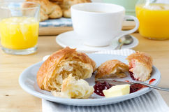 Continental Breakfast Setting on Wooden Table. Continental Breakfast table setting laid with croissants, orange juice and coffee. A serving of partly eaten Stock Images