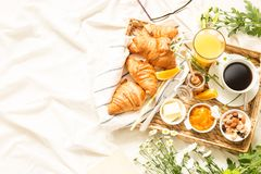 Continental breakfast on white bed sheets - flat lay. Continental breakfast on white bed sheets. Coffee, orange juice, croissants, jam, honey and flowers on Royalty Free Stock Photography