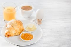 Free Continental Breakfast With A Croissant, Boiled Egg. Coffee Or Tea With Milk, A Glass Of Juice, Buns, Butter, Jam Royalty Free Stock Image - 103444146