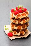 Continental classics belgian butter waffles with raspberries on. Black stone background stock photography
