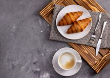 Flatlay of croissant, a cup of coffee at wooden tray with napkin on a gray stone concrete table. Continental traditional breakfast. Flatlay of croissant, a cup stock photos