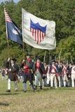 Continentals auf dem Marsch mit amerikanischen Flaggen Lizenzfreie Stockfotos