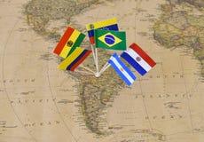 Continente del Sudamerica con i perni della bandiera degli stati sovrani sulla mappa fotografia stock