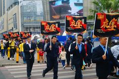 A contingent of billboards on the streets of Shenzhen. The shopping mall carries out a big sale of goods, and the staff of the market hold the billboard in the Stock Image